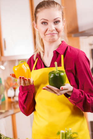 Young woman holding bell pepper vegetable thinking about meal or choosing good veggie.