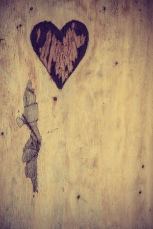 Small heart shape in piece of wood. Romantic detail close up concept.