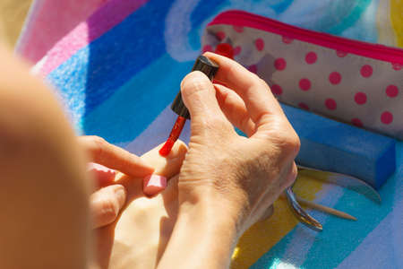 Woman relaxing doing her pedicure with red nail polish on beach towel. Female taking care of feet Standard-Bild