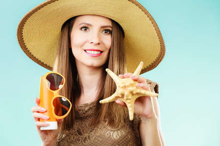 Holidays summer fashion and skin care concept. Woman in straw hat holds sunglasses shell and sunscreen lotion, blue background Foto de archivo