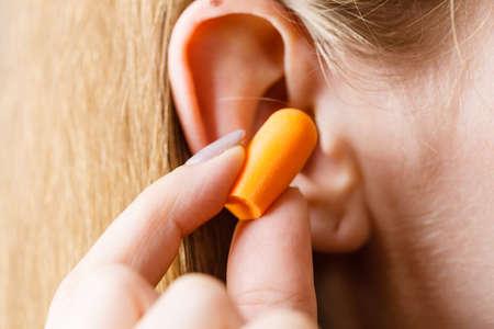 Donna che mette i tappi per le orecchie nelle orecchie per sbarazzarsi del rumore in un luogo rumoroso.
