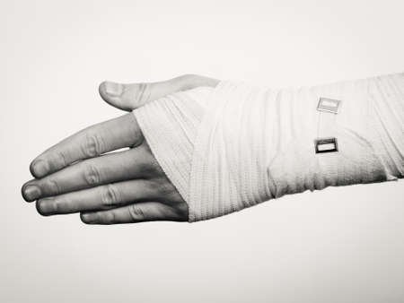 Fractures and dislocations concept. Male hand in white bandage. Helpful medication for painful palm arm of young man. Stok Fotoğraf