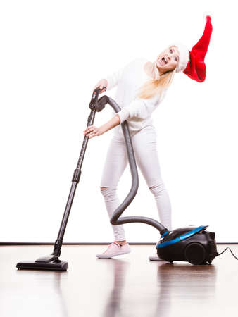 Woman vacuuming the house. Funny teen girl in santa helper hat with vacuum cleaner. Christmas time and housework concept. Stock Photo