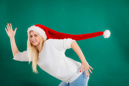 Christmas accessories, fun and joy concept. Woman wearing windblown long Santa hat, fooling around running somewhere. Studio shot on green background Stock Photo