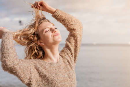 Happy smiling blonde woman portrait. Joyful female being positive walking outdoor wearing sweater having wind tousled hair in sunlight,