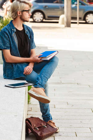 Male fashion, student concept. Guy holding notebook wearing jeans outfit and eccentric sunglasses sitting on white ledge next to modern building