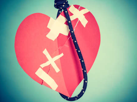 Small red heart shaped piece of paper on rope. Suicide, breakup, bad relationship, toxic romance, cardiology concept.