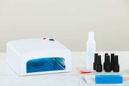 Professional gel hybrid manicure with led uv lamp set at beautician salon. Beauty wellness spa treatment objects concept