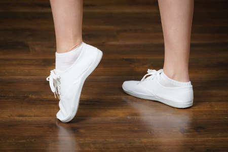 Unrecognizable woman wearing white bright sneakers trainers and socks standing on shiny wooden floor.