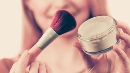 Fashionable cheerful young female holding professional powder brush, adding last touch to her make up Foto de archivo