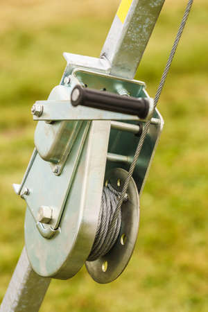 Close up of metal rope hooked on the reel, detail industrial agricultural objects