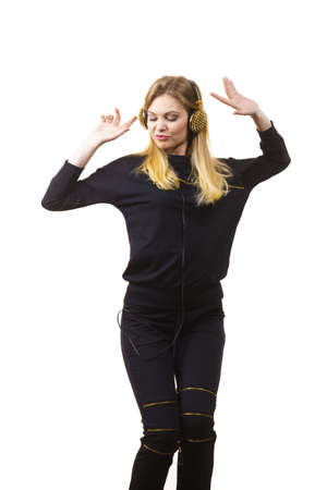 Teenager young grunge woman wearing black and listening to music on headphones with spikes, having fun dancing.