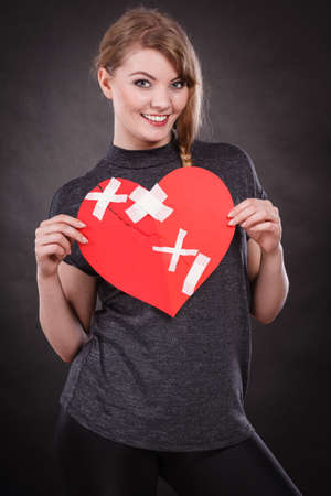 Healed love. Valentines Day concept. Young smiling woman holding big red heart with plaster. Girlfriend healing relationship. Stock fotó - 112417783