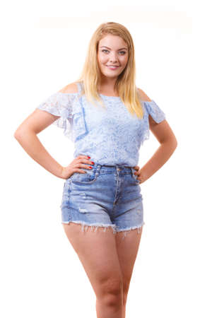 Pretty joyful teen presenting fashion. Young woman wearing stylish blue top and short jeans shorts. Standard-Bild
