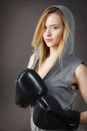 Sportsmanship fairplay and strong body. Young woman fighting boxing. Blonde girl wearing black punch gloves. Sport and fitness, power, exercising, on gray Stock Photo