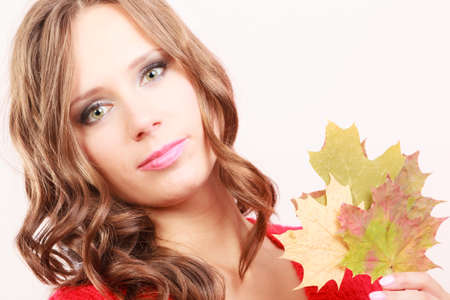 Beauty female autumnal model. Attractive girl long hair wearing warm red sweater with maple leaves in hand Foto de archivo