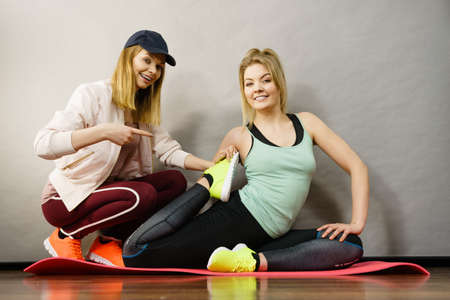 Young blonde woman in sportswear stretching body, working out with her female trainer.