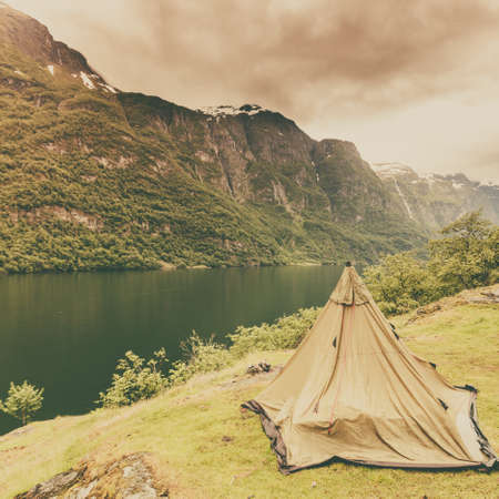 Tourism vacation and travel. Mountains landscape fjord and tent on warer shore, Norway Scandinavia Europe. Beautiful nature Stok Fotoğraf