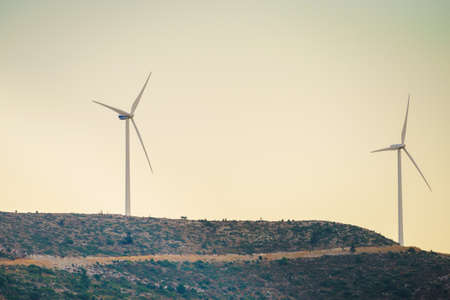 Windmills on Greek hills. Wind farm, source of renewable green energy in Europe. Ecologogy concept.