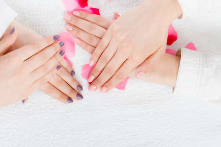Unrecognizable woman presenting her beautiful painted gel hybrid nails. Nail care concept.