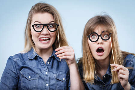 Two happy women holding fake eyeglasses on stick having fun fooling around wearing jeans shirts. Photo and carnival funny accessories concept. Imagens