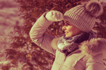 Pretty young woman wearing warm accessories during winter time. Female having grey beanie warm hat with pompons and blue scarf looking in distance