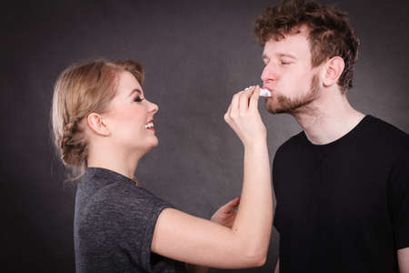 Hygiene and skincare concept. Protection and help in relationship. Smiling happy woman wipe cream face nose of funny man by hygienic tissue. Girlfriend takes care of her boyfriend. 免版税图像