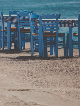 Seaside blue table and chairs open cafe outdoor restaurant in Greece on sea shore. Summer vacation on resort. 写真素材