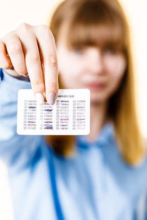 Woman holding card with codes for online transfers. Internet shopping, account protection, banking concept.