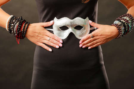 Holidays, people and celebration concept. Woman black dress with silver carnival venetian mask on dark background, part of body