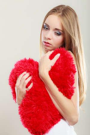 Broken heart love concept. Sad unhappy woman hugging red heart pillow closeup Reklamní fotografie
