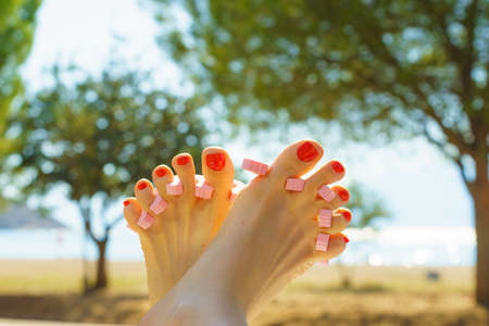 Woman waiting untill her feet nails dry on sun during summertime vacations. Female having toes separated.