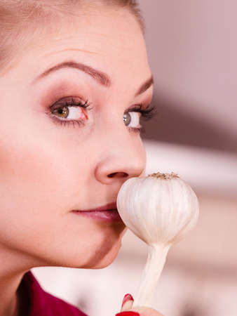 Woman holding healthy herb, two fresh natural garlic smelling it. Healthy eating and dieting concept. Stock Photo