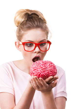 Funny silly weird woman in eyeglasses holding brain having something on mind, thinking of new concepts and ideas.