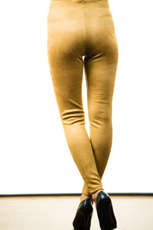 Unrecognizable woman wearing tight leggings pants mustard yellow brown well fitting skinny trousers Zdjęcie Seryjne