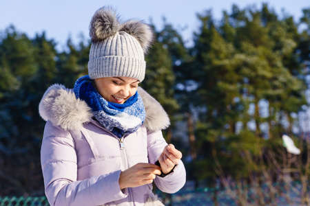 Pretty young woman wearing warm accessories during winter time. Female having grey beanie warm hat with pompons and pink jacket