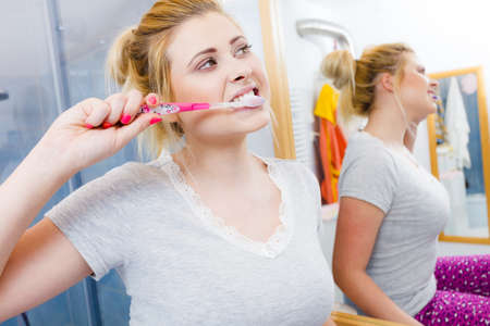 Woman brushing cleaning teeth closeup. Funny blonde girl with toothbrush in bathroom. Oral hygiene. Stok Fotoğraf