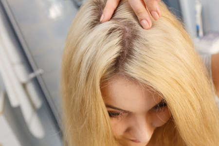 Woman showing her hair regrowth roots after blonde dying. Close up of female head.