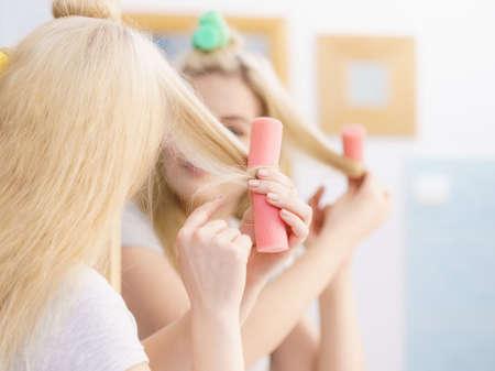 Blonde woman using hair rollers to create beautiful hairstyle on her hairdo. Standard-Bild