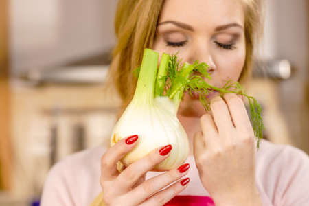 Woman in kitchen holding green fresh raw fennel bulb vegetable. Housewife cooking meal. Healthy eating, vegetarian food, dieting concept. Stok Fotoğraf
