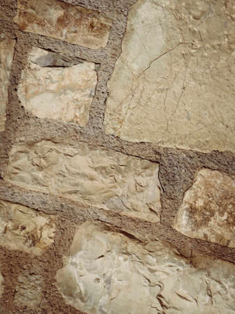 Wall made of stone bricks. Texture, background in the ancient style. Architectural details of Greece.