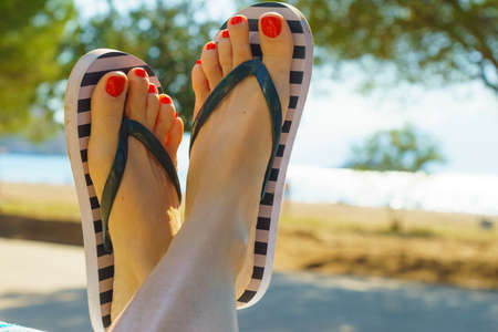 Unrecognizable woman wearing stripped flip flops and having painted toes with red nail polish. Female relaxing on beach.
