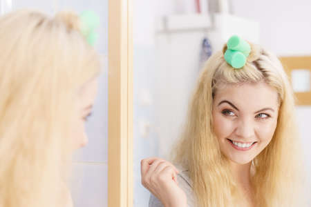 Blonde woman using hair rollers to create beautiful hairstyle on her hairdo. Imagens