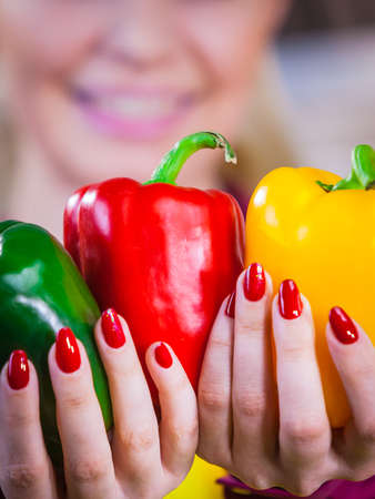 Woman hand holding bell pepper delicious healthy dieting vegetable presenting diet food in three colors