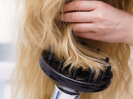 Unrecognizable woman with long blond hairdo using professional hair dryer. Hairstyling and haircare concept.