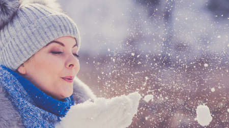 Pretty young woman blowing snow playing with it. Female having grey beanie warm hat with pompons and blue scarf.