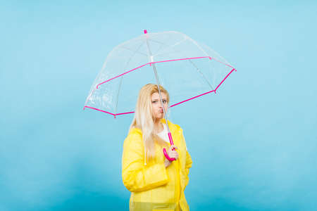 Sad bored blonde woman wearing yellow raincoat holding transparent umbrella waiting for rain.