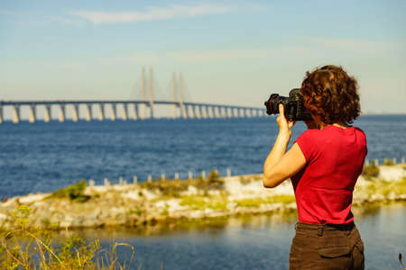 Oresundsbron. Tourist woman taking photo with camera from the Oresund bridge link between Denmark and Sweden Europe, Baltic Sea. Landmark and travel.