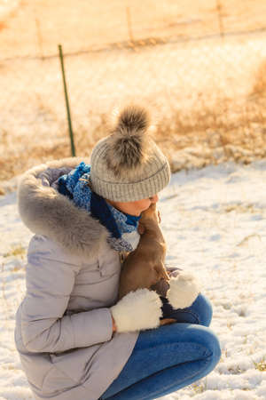 Young woman having fun outside in snow. Female playing with her small purebreed dog puppy in cold winter day.