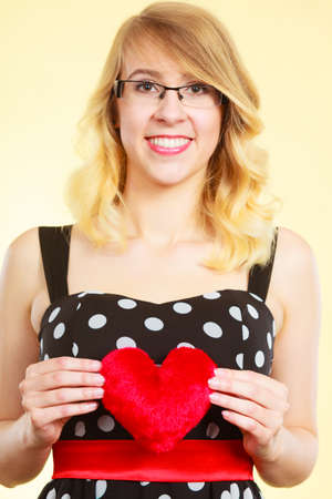 Woman blonde cute girl wearing dotted dress holding red heart love symbol studio shot on bright. Valentines day happiness concept